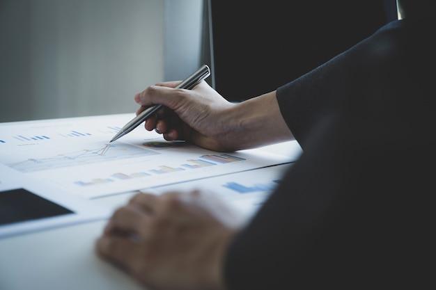 Kobieta interesu ręka trzyma pióro i analizuje wykres z laptopem w domowym biurze do wyznaczania ambitnych celów biznesowych