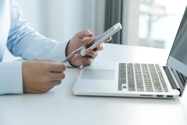 Kobieta interesu ręka trzyma smartphone i używa karty kredytowej do zakupów online