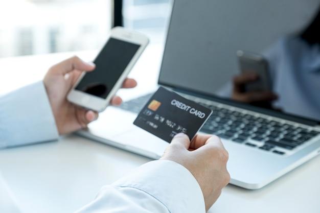 Kobieta interesu ręki trzymającej i używać karty kredytowej do zakupów online