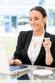 Kobieta interesu w kawiarni. atrakcyjna młoda kobieta w stroju formalnym pracuje na laptopie i uśmiecha się siedząc w kawiarni na chodniku