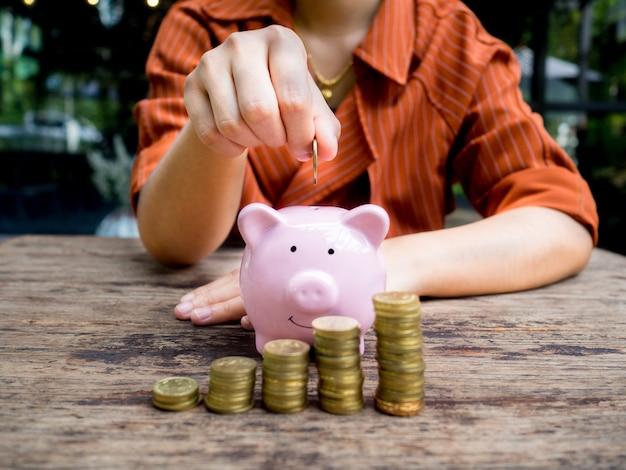 Kobieta interesu wkłada monetę do różowej skarbonki ze stosem złotych monet