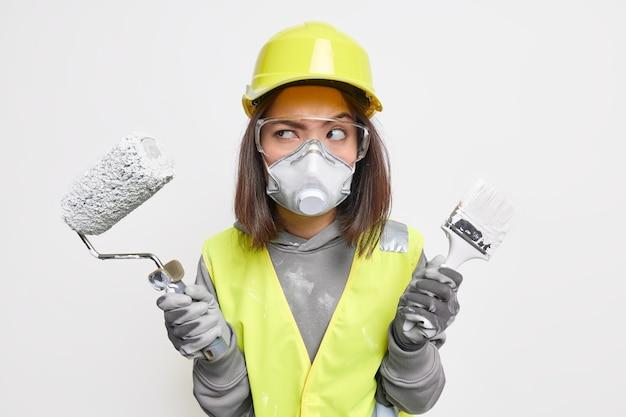Kobieta inżynier budowlana w kamizelce ochronnej okulary ochronne maska na kask i rękawice trzyma sprzęt wygląda poważnie na bok, gotowy do wejścia na teren budynku w celu kontroli. pracownik przemysłowy.