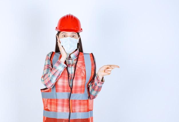 Kobieta inżynier budowy w czerwonym hełmie i masce ochronnej skierowana w prawo i wygląda na przerażoną.