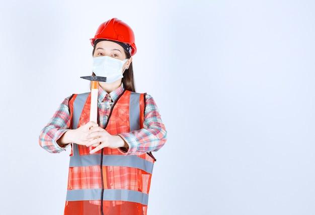Kobieta inżynier budowy w masce bezpieczeństwa i czerwonym hełmie trzyma drewnianą rękojeść topór.