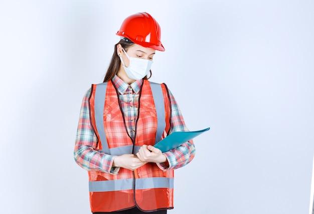 Kobieta inżynier budowy w masce bezpieczeństwa i czerwonym kasku trzyma niebieski folder.