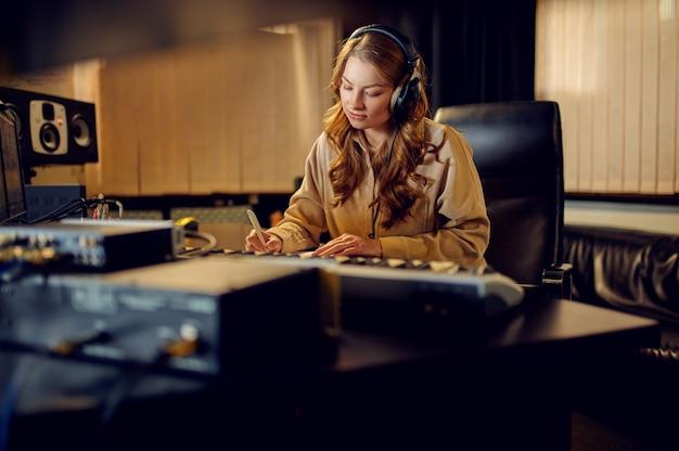 Kobieta inżynier dźwięku w słuchawkach, wnętrze studia nagrań na tle. syntezator i mikser audio, miejsce pracy muzyka