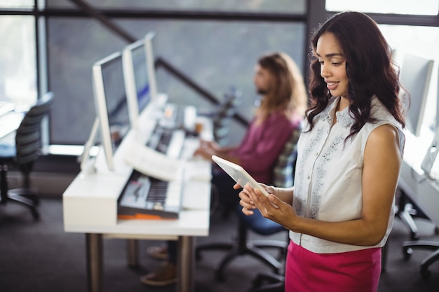 Kobieta inżynier dźwięku w studio za pomocą cyfrowego tabletu
