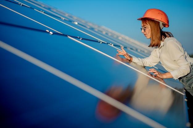 Kobieta inżynier stojący w pobliżu paneli słonecznych na zewnątrz
