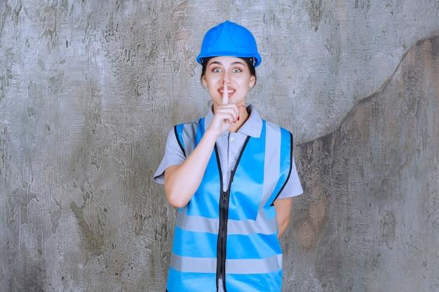 Kobieta inżynier ubrana w niebieski hełm i sprzęt i prosząca o ciszę.