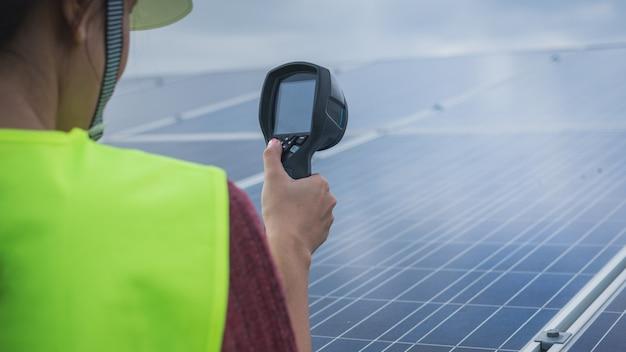 Kobieta inżynier używa termicznego imager sprawdzać temperatury upał panel słoneczny