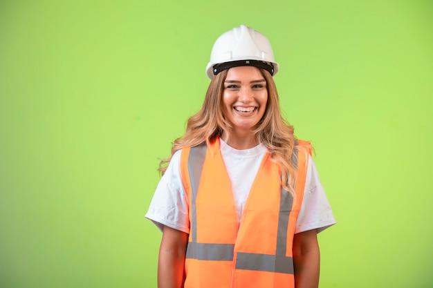 Kobieta inżynier w białym kasku i sprzęcie wygląda pozytywnie.