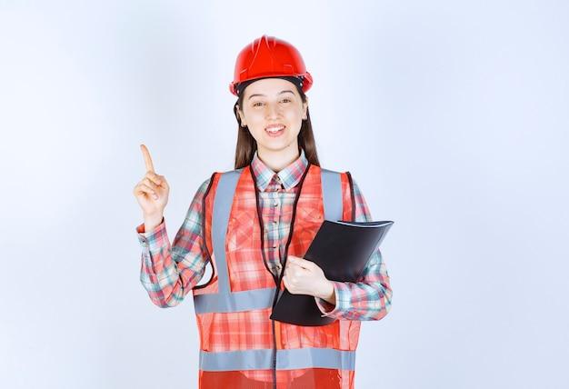 Kobieta inżynier w czerwonym hełmie trzymająca czarny plan projektu i mająca dobry pomysł.