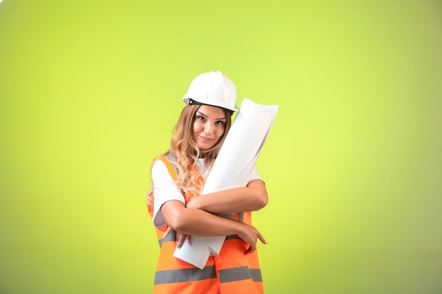 Kobieta inżynier w kasku i sprzęcie, trzymając plan budowy.