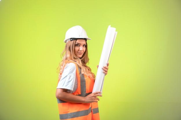 Kobieta inżynier w kasku i sprzęcie trzymająca plan budowy i wygląda pewnie.