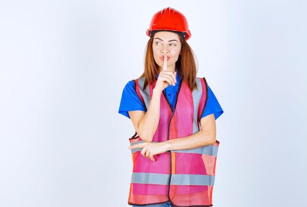 Kobieta inżynier w mundurze i czerwonym kasku z prośbą o ciszę.
