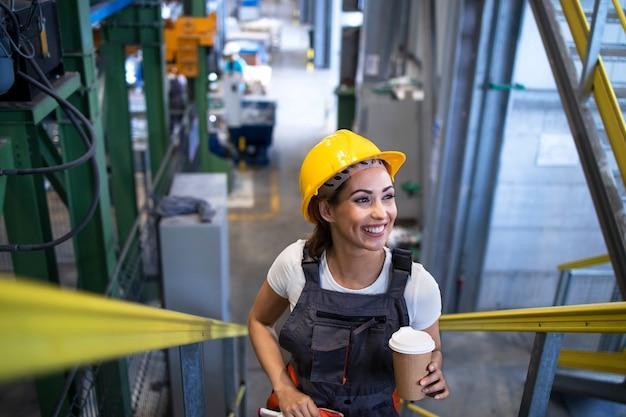 Kobieta-inżynier w mundurze i kasku wspinaczkowym wspinająca się po metalowych stopniach hali fabrycznej.