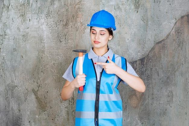 Kobieta inżynier w niebieskim biegu i hełmie, trzymając siekierę z drewnianą rączką.