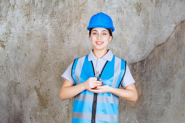 Kobieta inżynier w niebieskim biegu i kasku trzyma szczypce do prac naprawczych.