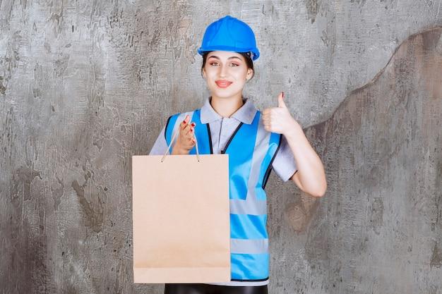 Kobieta inżynier w niebieskim kasku i sprzęt, trzymając tekturową torbę na zakupy i pokazując kciuk do góry.