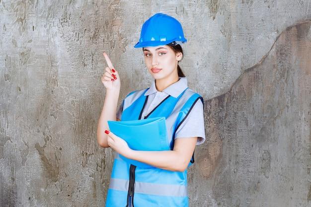 Kobieta inżynier w niebieskim mundurze i hełmie trzyma niebieski folder raportu i wskazuje na kogoś w pobliżu.