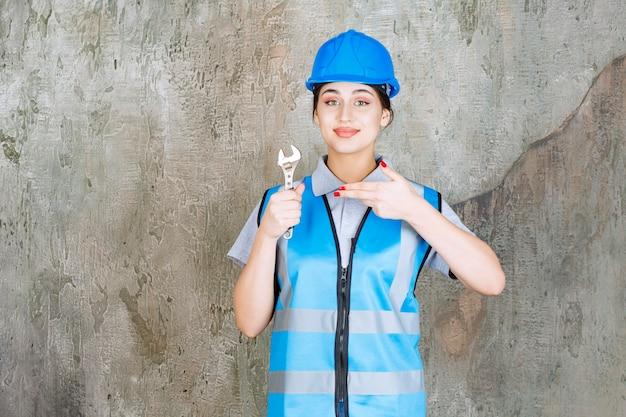 Kobieta inżynier w niebieskim mundurze i hełmie, trzymając metalowy klucz.