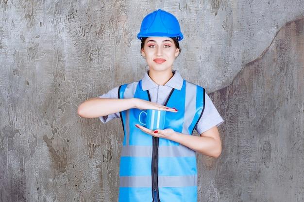 Kobieta inżynier w niebieskim mundurze i hełmie, trzymając niebieski kubek herbaty.