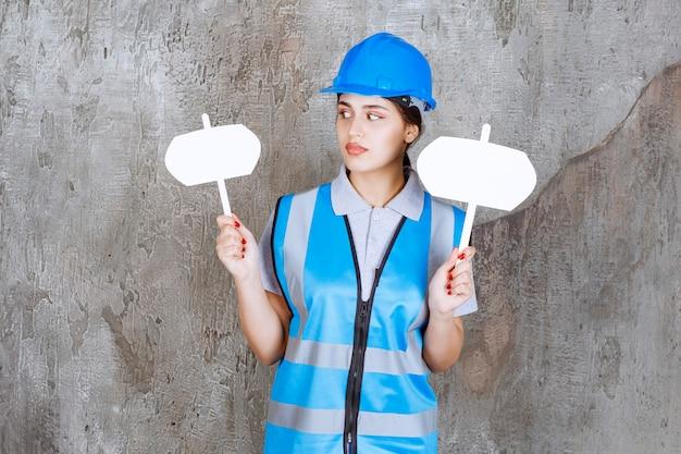 Kobieta inżynier w niebieskim mundurze i hełmie, trzymając w obu rękach dwie puste tablice informacyjne.