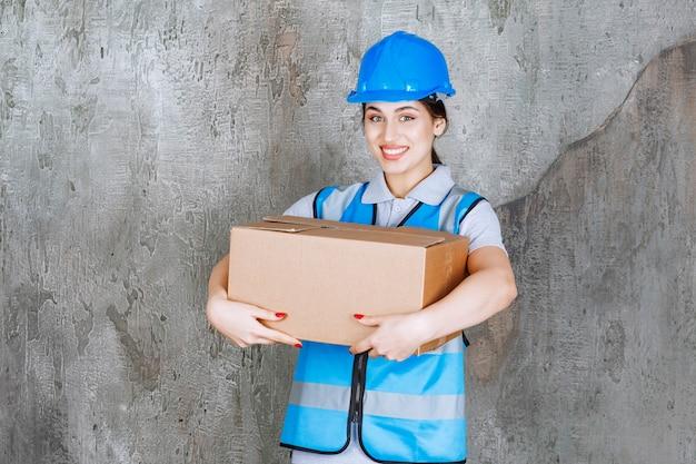 Kobieta inżynier w niebieskim mundurze i hełmie trzymająca kartonową paczkę.