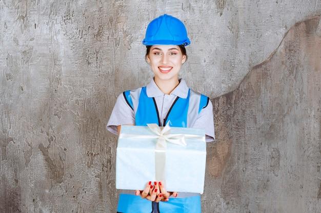 Kobieta inżynier w niebieskim mundurze i kasku trzyma niebieskie pudełko.