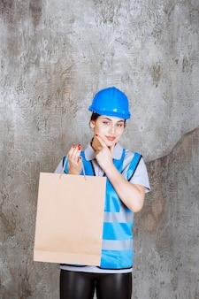 Kobieta inżynier w niebieskim mundurze i kasku trzyma torbę na zakupy i wygląda zamyślona.