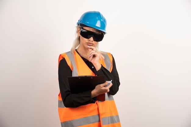 Kobieta inżynier w okularach patrząc na schowek na białym tle. wysokiej jakości zdjęcie