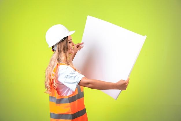 Kobieta inżynier w planie projektu czytania białego kasku i przekładni.