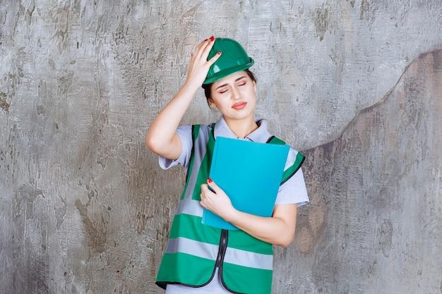 Kobieta inżynier w zielonym hełmie trzyma niebieski folder i wkłada rękę do głowy, gdy jest zmęczona.