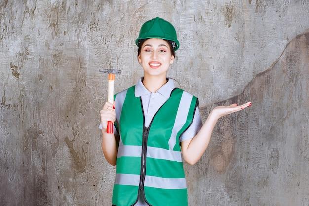 Kobieta inżynier w zielonym hełmie trzymając siekierę z drewnianą rączką do naprawy.
