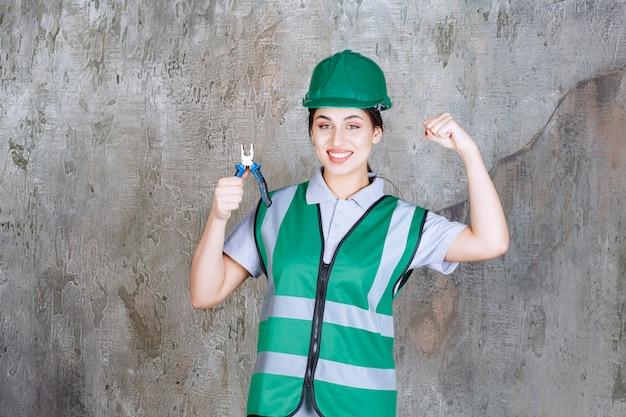 Kobieta inżynier w zielonym kasku trzymając szczypce do naprawy i pokazując pięść.