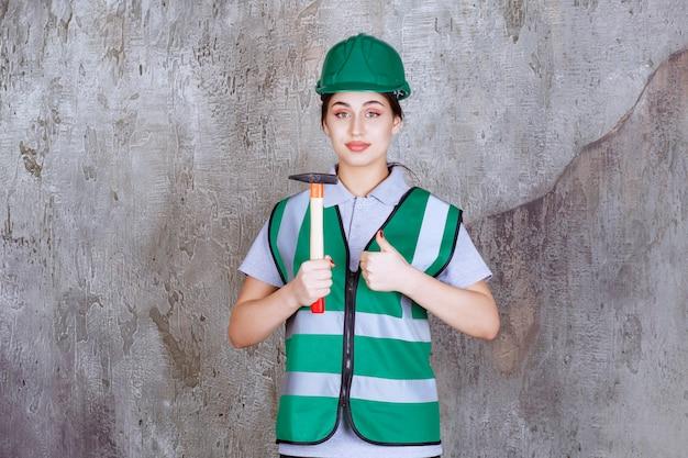 Kobieta inżynier w zielonym kasku trzymająca siekierę z drewnianą rękojeścią do naprawy i pokazująca pozytywny znak ręki.