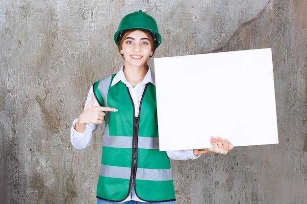 Kobieta inżynier w zielonym mundurze i hełmie, trzymając prostokątną tablicę informacyjną.