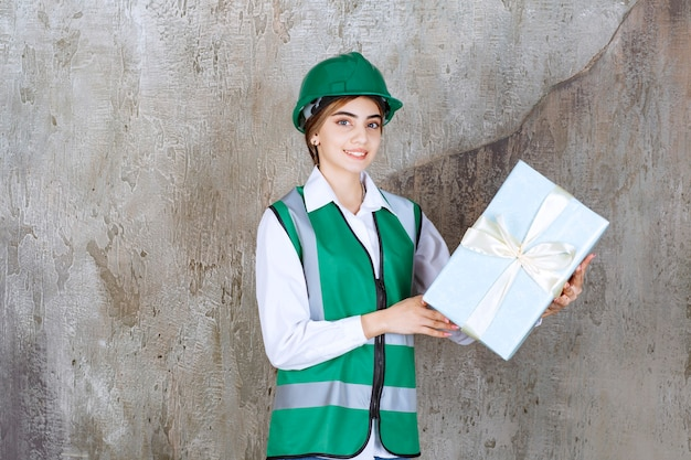 Kobieta inżynier w zielonym mundurze i kasku trzyma niebieskie pudełko.