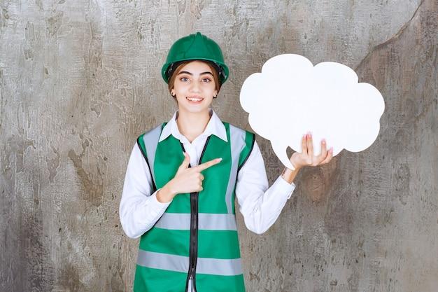 Kobieta inżynier w zielonym mundurze i kasku trzyma tablicę informacyjną w kształcie chmury.