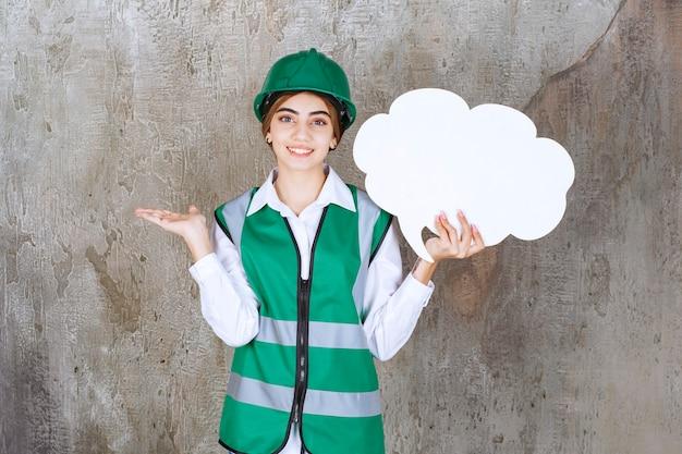 Kobieta inżynier w zielonym mundurze i kasku, trzymając tablicę informacyjną w kształcie chmury.