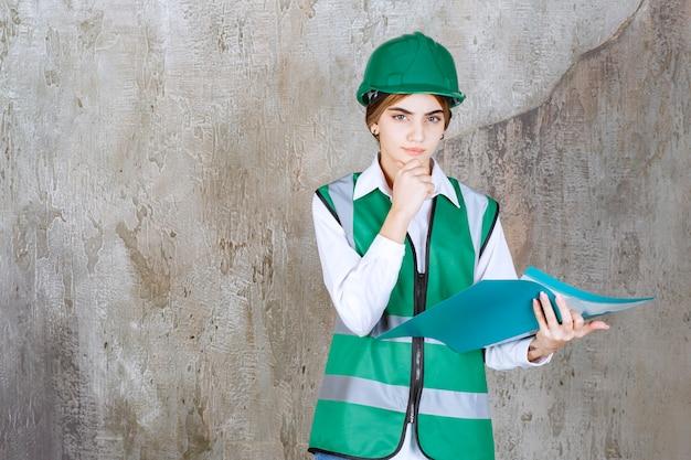Kobieta inżynier w zielonym mundurze i kasku, trzymając zielony folder projektu, myśląc i analizując.