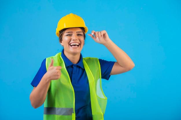 Kobieta inżynier w żółtym kasku i przekładni czuje się pozytywnie.