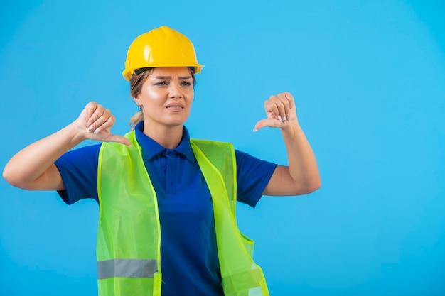 Kobieta inżynier w żółtym kasku i przekładni robi kciuki w dół.
