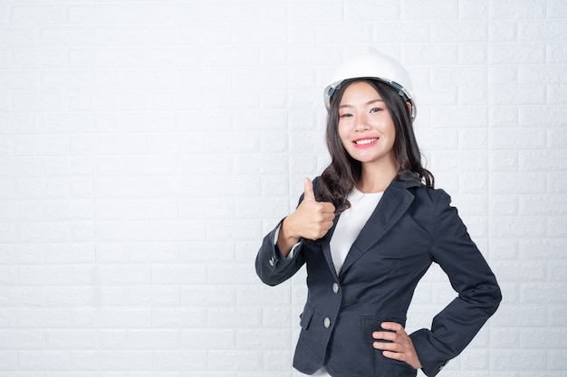 Kobieta inżynierii trzyma kapelusz, oddziel białe ściany z cegły wykonane gesty z języka migowego.