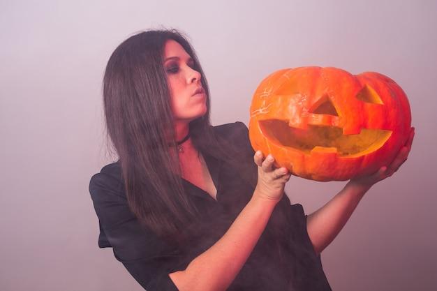 Kobieta jako czarownica stoi z dynią halloween i karnawałową koncepcją.