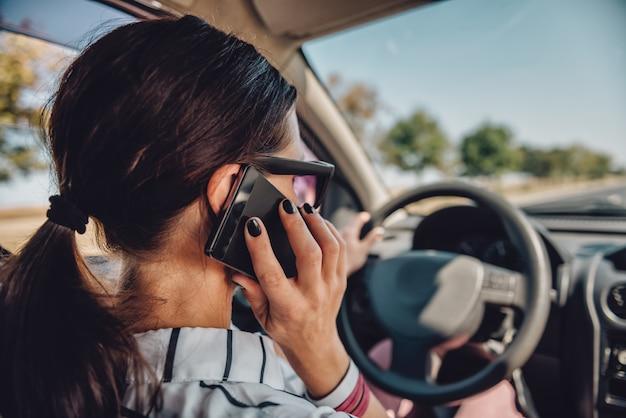 Kobieta jazdy samochodem i rozmowy na smartfonie