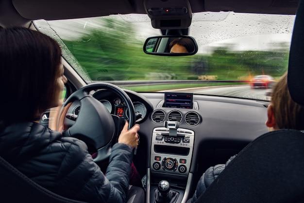 Kobieta jazdy samochodem za rogiem w deszczu