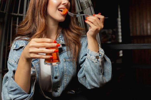 Kobieta je dżemu pigwy i trzyma szkło czarna herbata