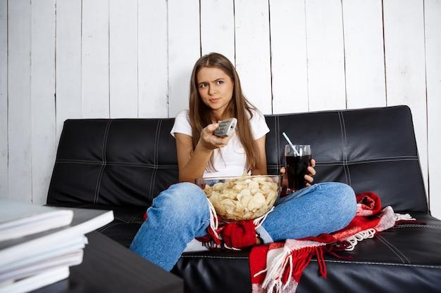 Kobieta je frytki, pije napoje gazowane, ogląda telewizję, siedzi na kanapie.