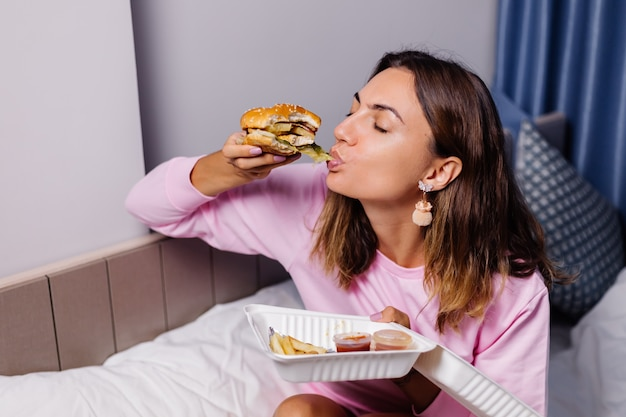 Kobieta je hamburgera w domu